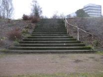 1970-luvulla rakennetut raskaat betoniportaat jätettiin puroputouksen tukirakenteeksi. Hankalahoitoinen, ruma rinne pengerrettiin kahdella graniittimuurilla. (kuva: Kotkan puistotoimen arkisto)